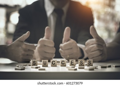 Selected focus SUCCESS word on wood blocks text with blured image of bussines group background