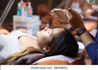 Selected focus teenage doing eyelash extension in beauty shop