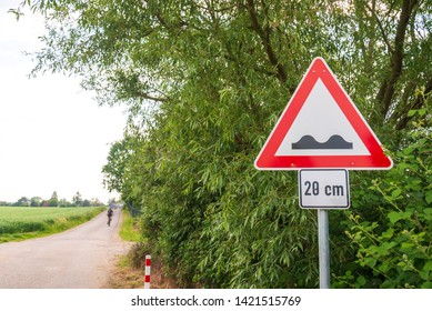 Selected focus view at speed bump sign, warning and caution symbol to be careful the bumpy road in countryside surrounded with agricultural field and range of bush and shrub against cloudy sky.