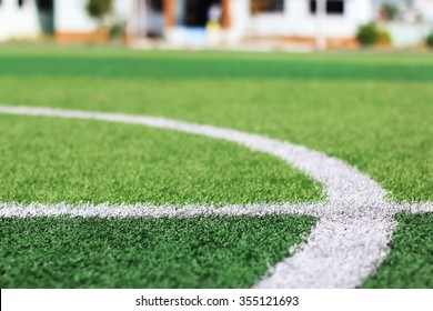 selected focus at white line on green synthetic grass indoor soccer field with blur building behind