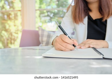 selected focus woman hand writing with pen in spiral notepad on bright desktop, education ,business concept