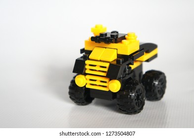 Selected focused of a toy lorry made of yellow and black plastic block.