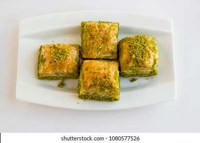 Selected traditional Turkish dessert baklava,of Ramadan table.White surface,isolated.Top view in white porcelain plate.