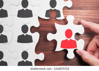 Selecting person for the job. Personnel, employment and recruitment concept.Human resource management. Assembling jigsaw puzzle on wood desk.