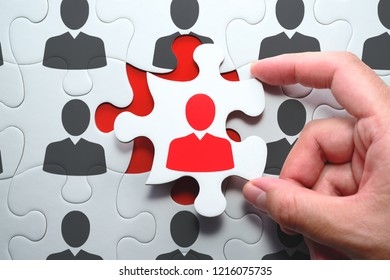 Selecting right people for organization's success. Think different and unique concept. Putting last jigsaw puzzle piece with red businessperson.