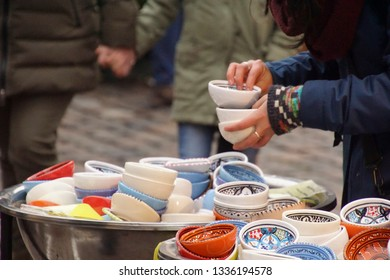 Selecting small porcelain bowls in Chritmas market of Heidelberg, Germany
