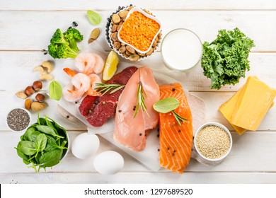 Selection of animal and plant protein sources - fish, meat, beans, cheese, eggs, nuts and seeds, kale, on wood background