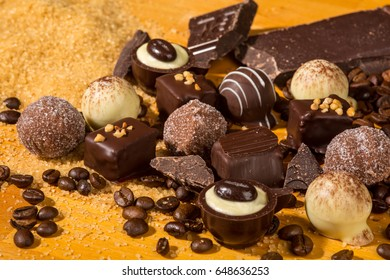 A selection of assorted chocolate truffle pralines decorated on a wooden table with dark chocolate, brown sugar and coffee beans, indicating mayor ingredients.