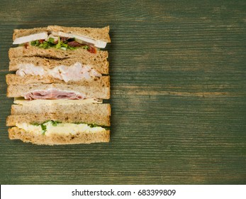 Selection of Assorted Sandwiches in Brown Bread Against a Green Wooden Background