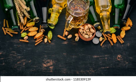 A selection of beer and snacks. Light beer, dark beer, live beer. On a black wooden background. Free space for text. Top view.