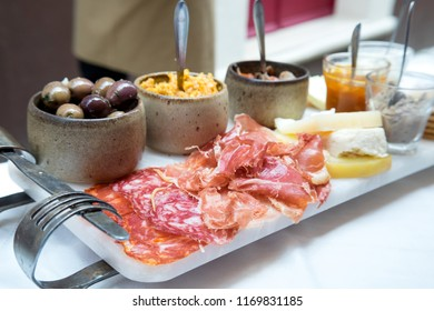 A selection of best appetizers of Portugal food or portuguese tapas - smoked ham, salami, chorizo sausages, a variety of cheese, crackers, liver pate and several traditional kinds of jam