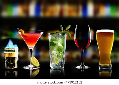 Selection of best selling drinks beer glass of wine  cocktails martini mojito and shot short  bar blurred background