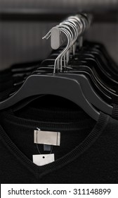 A selection of black V-neck shirts hanging on a clothes rail by coat hangers. The identical shirts are all new with labels attached.