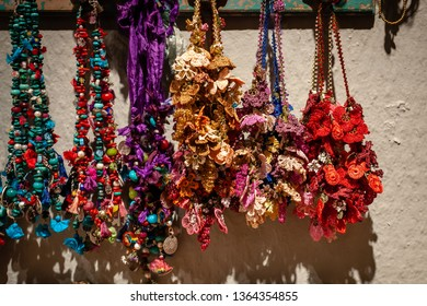 Selection of bright and colorful necklaces designed with hand made oya, Turkish needle lace, a traditional Anatolian hand craft, hanging from a wooden bar against an off white colored wall