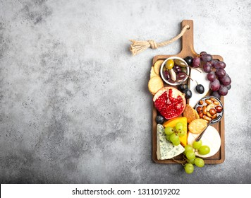 Selection of cheese and appetizers, camembert, brie, cheddar, bread, cracker, grapes, nuts, honey. Assorted mix of cheese on rustic wooden board with space for text, top view, close-up
