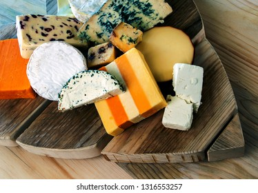 Selection of cheeses on natural, rustic, cheese board.