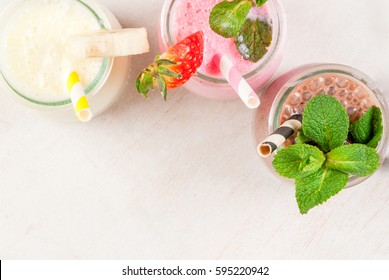 Selection of classic milkshakes in small jars: chocolate, strawberry, banana. On a white wooden table, with tubes, copy space top close view