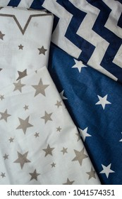 A selection of coarse calico fabrics with geometric patterns for sewing pillows. Folded fabric laid out on the table. Coloring for the boy. Close up photo. Dark blue and white color.