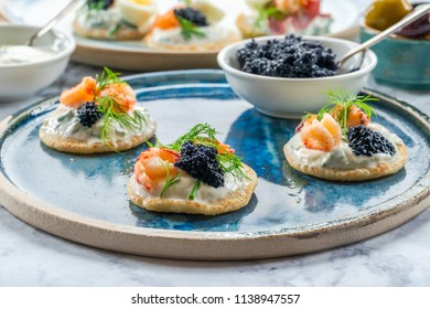 Selection of cocktail blinis with salmon, crayfish, caviar and sour cream - gourmet party food