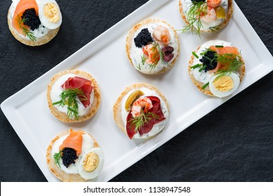 Selection of cocktail blinis with salmon, cured bresaola, crayfish, caviar, quail eggs and sour cream - gourmet party food - top view