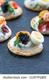 Selection of cocktail blinis with salmon, cured bresaola, crayfish, caviar, quail eggs and sour cream - gourmet party food.