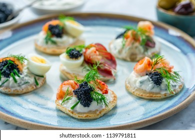 Selection of cocktail blinis with salmon, cured bresaola, crayfish, caviar, quail eggs and sour cream - gourmet party food