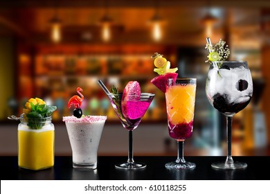 Selection of cocktails drinks alcohol martini spritz bramble gin tonic bar blurred background