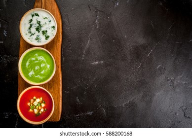 Selection of cold refreshing summer soups: tomato gazpacho, tarator, cream soup of green peas on a cutting board on a black concrete table top view copy space