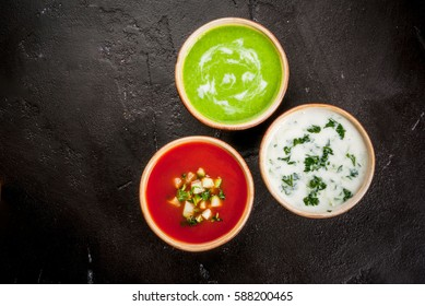 Selection of cold refreshing summer soups: tomato gazpacho, tarator, cream soup of green peas on a black concrete table top view copy space