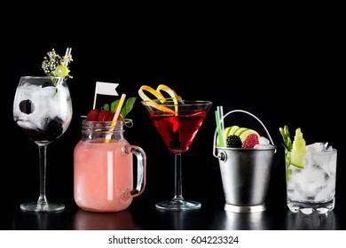 selection collage of rustic colourful various cocktails alcoholic drinks garnish decoration fresh fruit white flag plain black background