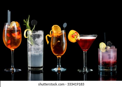 Selection of colorful Cocktails with garnish from tall to low isolated on black background