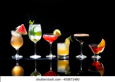 Selection of colorful festive Christmas drinks, alcoholic beverages and cocktails in elegant glasses on a dark background with copy space