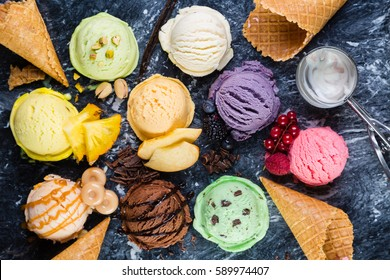 Selection of colorful ice cream scoops on marble background, top view