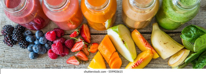 selection of colorful smoothies on rustic wood background, copy space