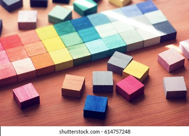 Selection of colors. colorful  color sample cubes arranged on a wooden table. Focus on foreground.