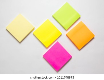 A selection of coloured sticky note pads isolated on an off white background