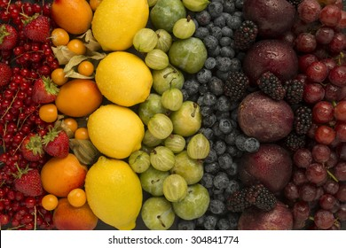 A selection of colourful fruits arranged as rainbow colours
