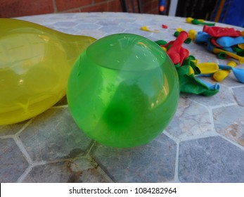 selection of colourful water balloons, some blown up some empty on outdoor table ready for water fight