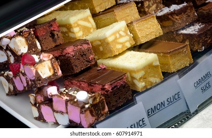 A selection of delicious cake slices for sale with white labels in a cafe window