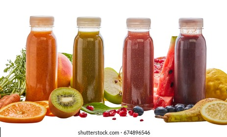 Selection of different energising fruit smoothies in four bottles surrounded by fresh ingredients with pear, orange, watermelon, pomegranate, kiwi, mango, carrot and apple on white for a healthy diet