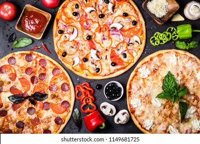 selection of different pizzas on a black background and ingredients. Peperoni, Vegetarian and Seafood Pizza.