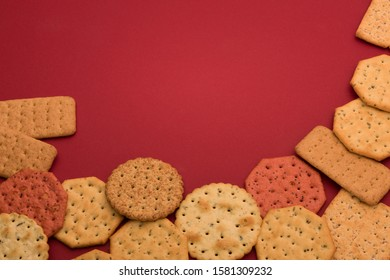 Selection of different type of crackers or water biscuits. Flat, dry baked food made with flour and seasoning. Red dark paper as the background.