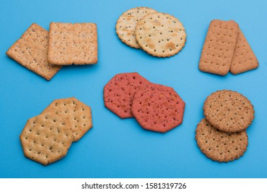 Selection of different type of crackers or water biscuits. Flat, dry baked food made with flour and seasoning. Blue paper as the background.
