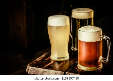 Selection of different types of beer in glasses in pub background, copy space