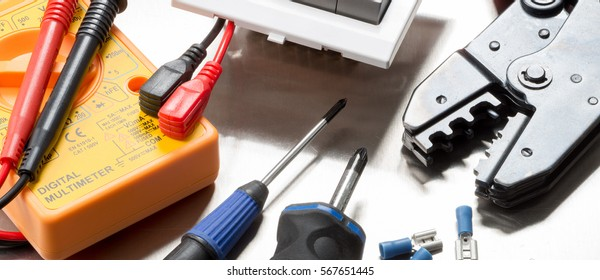 Selection of electrical contractors tools including wire cutters, multimeter, screwdrivers, clips and a light switch. Website banner format.