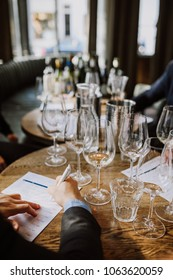 A selection of empty wine glasses on the wooden table in a restaurant, man taking notes at the wine training course. Learning concept, vertical image.