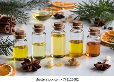 Selection of essential oils with Christmas spices and ingredients - spruce, fir, frankincense resin, star anise, cinnamon, dried orange slices