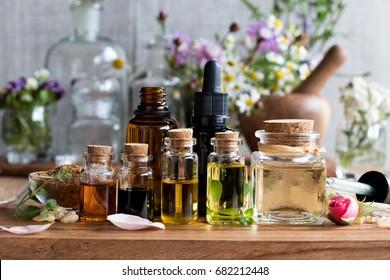 Auswahl der ätherischen Öle mit Kräutern und Blumen im Hintergrund