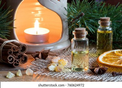 Selection of essential oils with star anise, clove, cinnamon sticks, frankincense resin, dried orange slice, an aroma lamp and pine branches in the background