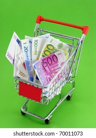 A selection of euro currency in a shopping trolley on a coloured background